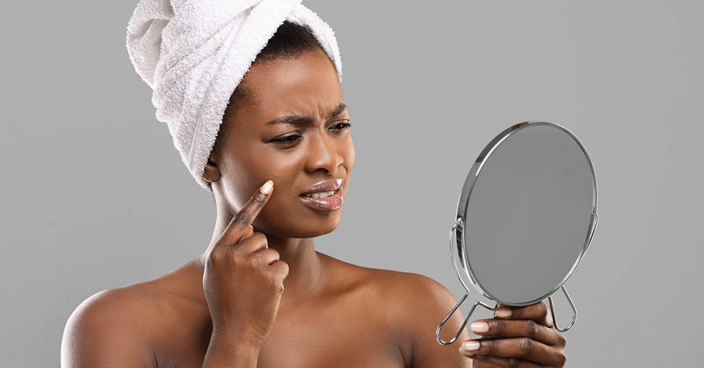 Woman just out of shower examining her complexion in mirror